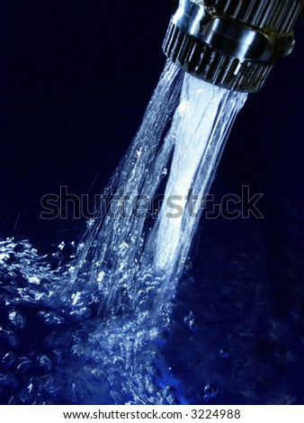 Faucet with sparkling blue water and lots of bubbles - stock photo