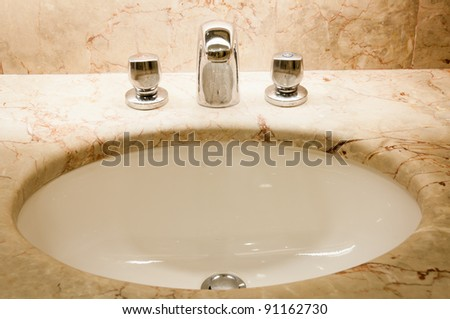 Faucet with two handles and white sink - stock photo