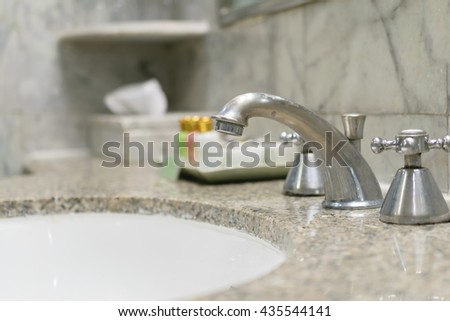 Faucets with blurry images of liquid soap background.