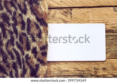 faux fur leopard and empty paper tag lying on a wooden table - stock photo