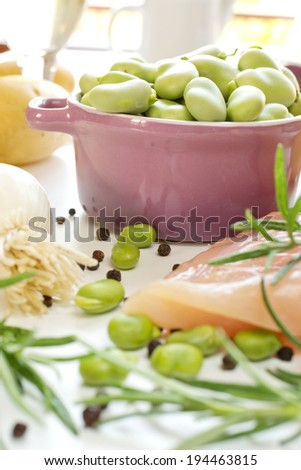 Fava beans in lilac casserole with ingredients - stock photo
