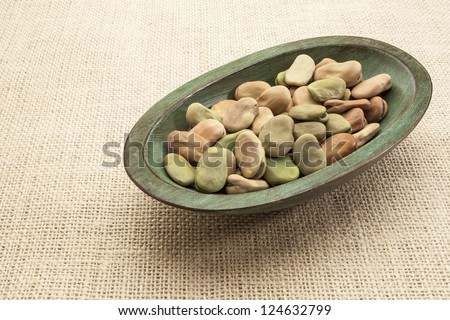 fava (broad) beans  in a rustic wood bowl against burlap canvas - stock photo
