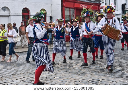 FAVERSHAM, UK-SEPTEMBER 1:  Morris dancers with harvest decorated hats,in the parade at the annual Hop Festival, which celebrates the hop picking tradition in Kent. September 1, 2013 , Faversham,  UK. - stock photo