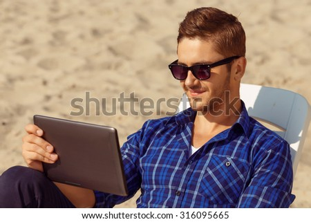 Favorite film.  Pleasant handsome freelancer lying on the sun bed and holding laptop while resting on the beach - stock photo