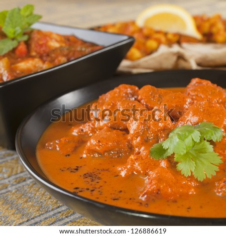 Favourite Indian curry Rogan Josh with chapatis and channa dhal, and chicken jalfrezi. - stock photo