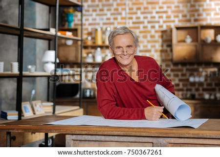 Favourite job. Cheerful elderly delighted man holing his blueprint and smiling while enjoying his job