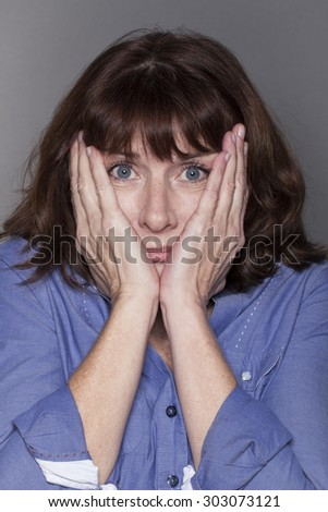 fear concept - attractive mature woman hiding her cheeks with both hands looking anxious and stressed out with eyes wide opened,closeup in studio shot - stock photo