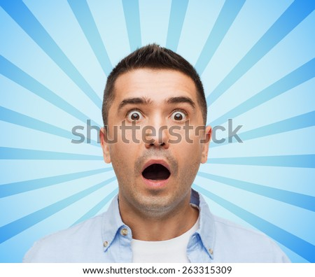 fear, emotions, horror and people concept - face of scared man shouting blue burst rays background - stock photo