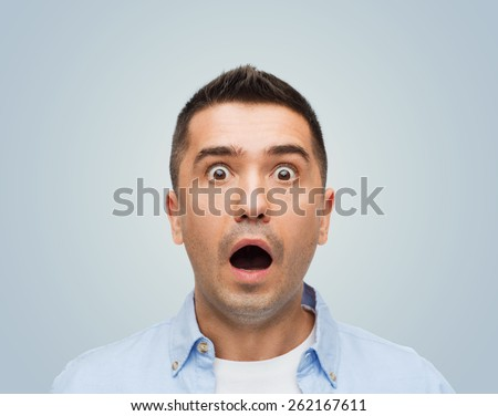 fear, emotions, horror and people concept - scared man with big eyes and open mouth shouting over gray background - stock photo