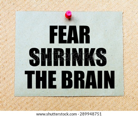 Fear Shrinks The Brain written on paper note pinned with red thumbtack on wooden board. Motivation conceptual Image - stock photo