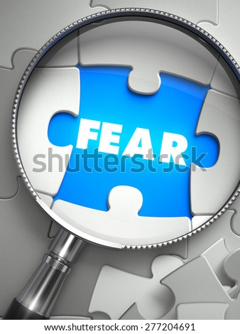 Fear - Word on the Place of Missing Puzzle Piece through Magnifier. Selective Focus. - stock photo