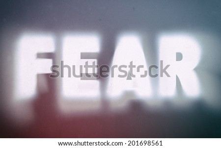 Fear word on vintage blurred background, concept sign