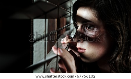 Fearful battered woman peeking through the blinds to see if her husband is home - stock photo