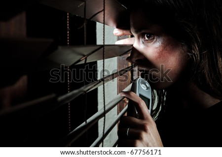 Fearful battered woman peeking through the blinds to see if her husband is home. she is contemplating whether to call the domestic violence hotline - stock photo