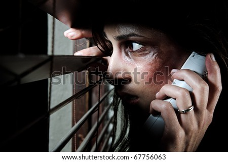 Fearful battered woman peeking through the blinds to see if her husband is home while calling for help - stock photo