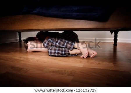 Fearful boy hiding under the bed - stock photo