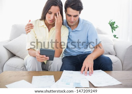 Fearful couple doing their accounts sat on a couch - stock photo