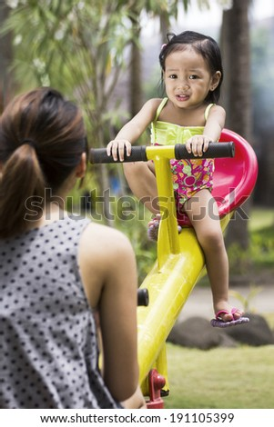 Fearful girl riding on a park seesaw with a woman. - stock photo
