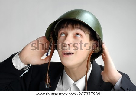 Fearful Teenager in Military Helmet on the Grey Background