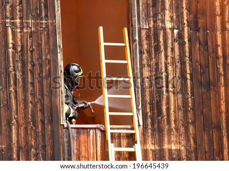 fearless firefighter with hydrant delivers plenty of water when switching off a fire in a House - stock photo