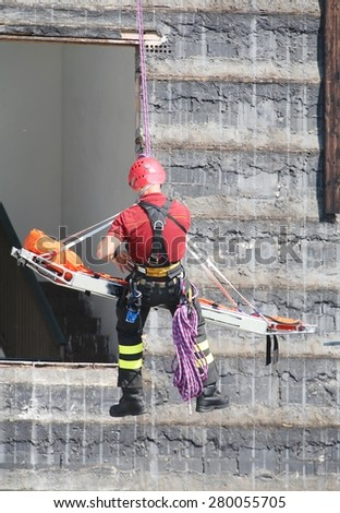 fearless fireman during an exercise carries the stretcher with the climbing rope - stock photo