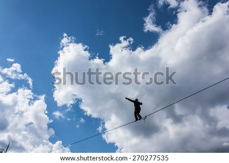 Fearless highliner walking on tight rope on vibrant blue sky background - stock photo