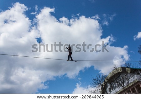 Fearless highliner walking on tight rope over the river on vibrant blue sky background - stock photo