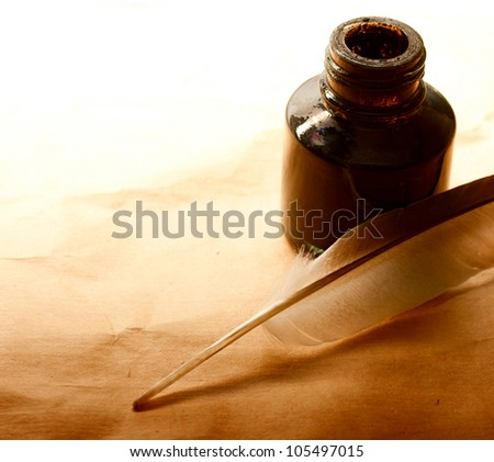 Feather and ink bottle on paper - stock photo