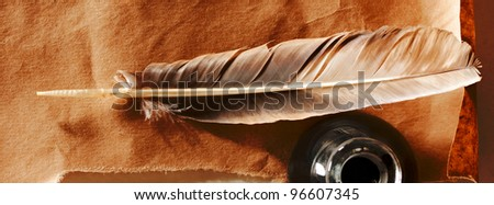 Feather and ink bottle on paper background - stock photo