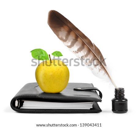 Feather in ink bottle and workbook with an apple - stock photo