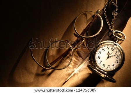 Feather near old spectacles and watch on paper surface under beam of light - stock photo