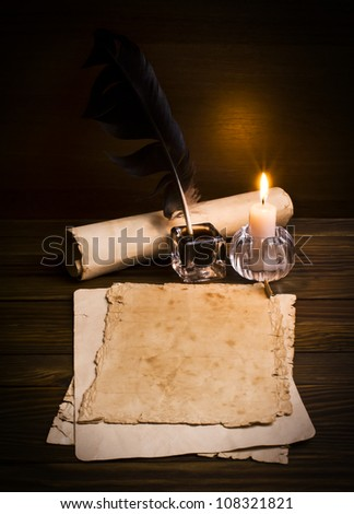 feather, old paper and candle on a wooden background - stock photo