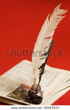 Feather quill and newspapers - stock photo