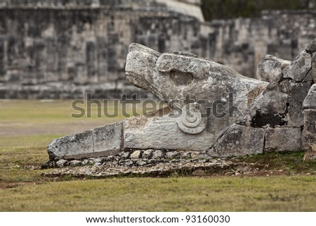 Feathered serpent at the foot of pyramid Kukulkan in Chich?n Itz - stock photo