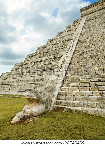 Feathered serpent at the foot of pyramid Kukulkan in Chichen Itza - stock photo