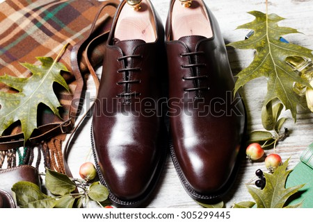 Featuring Typical Male Clothing and Accessories Still life with brown boots, leather belt and camera on aged textured boards A pair of luxury brown shoes closeup on wood background  - stock photo