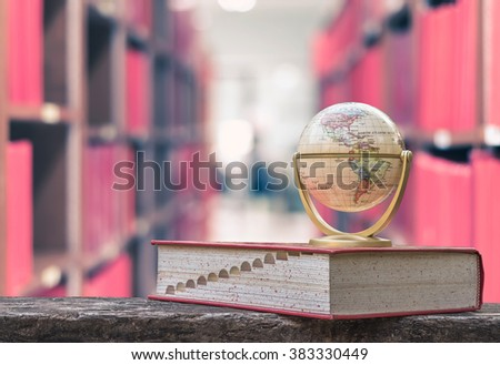 FEBRUARY 26, 2016 - BANGKOK, THAILAND: Globe model on textbook, book on old age wood table with vintage style blur abstract library background, stack of knowledge resource,  educational data aisle - stock photo