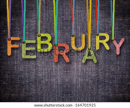 February letters hanging strings with blue sackcloth background. - stock photo