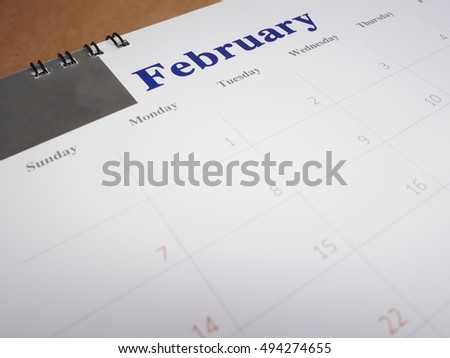 February on calendar page, desk calendar on wood background (Selective focus)