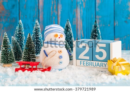 February 25th. Cube calendar for february 25 on wooden surface with snowman, sled, snow and fir - stock photo