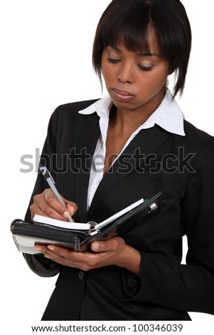 Fed-up businesswoman writing in her agenda - stock photo