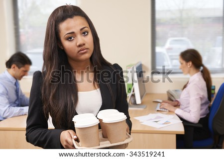 Fed Up Female Intern Fetching Coffee In Office - stock photo