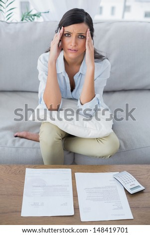 Fed up woman checking her bills in her living room - stock photo
