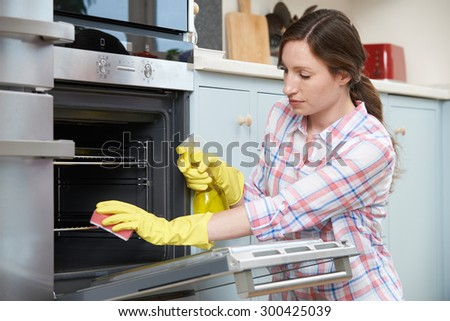Fed Up Woman Cleaning Oven At Home - stock photo