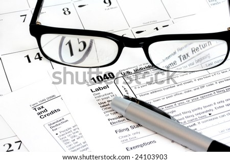 Federal income tax 1040 form on a calendar with the 15th noted.  Glasses and a pen sit on top.