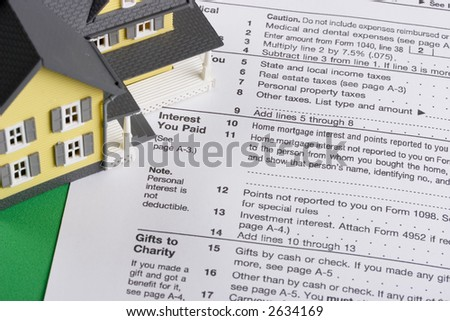 federal income tax form with colorful yellow house - mortgage interest deduction - stock photo