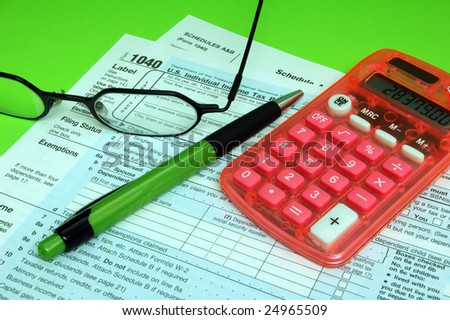 Federal Tax Forms with Pen and Calculator on Green Background