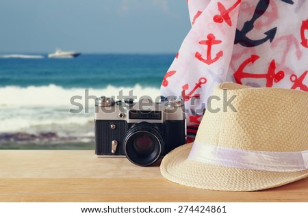 fedora hat, old vintage camera and scarf over wooden table and sea landscape background. relaxation or vacation concept  - stock photo