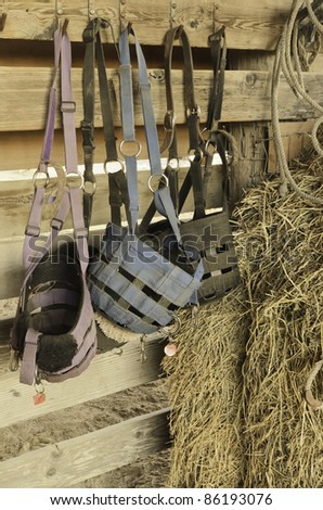 Feed bags of canvas and leather in horse stable - stock photo