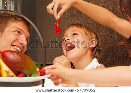feed me - mother feeding son with berries - stock photo